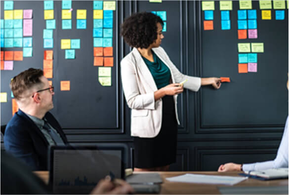 woman-placing-sticky-notes-during-meeting